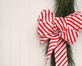 Christmas ribbon on beadboard a red and white striped and real garland a background with room for copyspace Stock Images