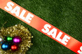 Christmas sale concept ornament on the green grass background Stock Image