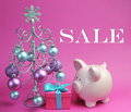 Christmas sale still life with pastel pink and blue with silver christmas tree and baubles gift piggy bank against a Royalty Free Stock Photo