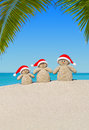 Christmas sandy Snowmen family in Santa hats at palm beach Royalty Free Stock Photo