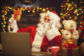 Christmas. Santa Claus with laptop reading letter