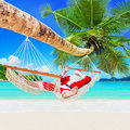 Christmas Santa Claus relax in hammock at tropical palm sandy ocean island beach Royalty Free Stock Photo