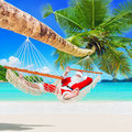 Christmas Santa Claus relax in palm shade hammock at tropical sandy ocean island beach Royalty Free Stock Photo