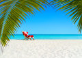 Christmas Santa Claus relaxing on sunlounger at ocean sandy tropical beach Royalty Free Stock Photo