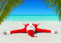 Christmas Santa Claus sunbathe at tropical ocean palm sandy beach Royalty Free Stock Photo