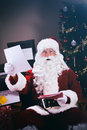 Christmas santa claus surprised at the naughty and nice list series with a man in a outfit in various poses with props Stock Photography