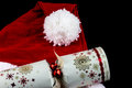 Christmas Santa Hat and Cracker on Black Background Royalty Free Stock Photo