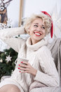 Christmas santa hat happy woman sitting in a chair smiling girl holding cup of tea her hand decorations Stock Images