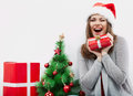 Christmas santa hat isolated woman portrait hold christmas gift beside green tree smiling happy girl seat against white Stock Photo