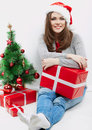 Christmas santa hat isolated woman portrait hold christmas gift beside green tree smiling happy girl seat against white Stock Photos