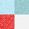 Christmas seamless patterns from snowflakes white on red blue turquoise and gray backgrounds Royalty Free Stock Image