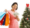 Christmas shopping big spender beautiful african american woman holding bags and money isolated on white in front of a tree Stock Image