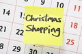 Christmas shopping reminder written on a yellow paper adhesive note stuck to a wall calendar background Royalty Free Stock Photo