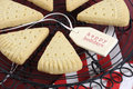Christmas shortbread triangle cookies on vintage baking rack closeup dark red rustic wood background with festive decorations Royalty Free Stock Images