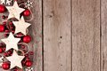 Christmas side border with rustic wood star ornaments and baubles on aged wood