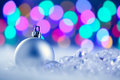 Christmas silver bauble in blurred lights Stock Photography