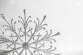 Christmas silver snowflake on abstract white glitter holiday background. Royalty Free Stock Photo
