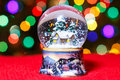 Christmas Snow Globe in front of Christmas tree lights closeup