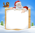 Christmas snow scene santa sign a with claus and a cute cartoon robin above a wooden Stock Photo