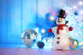 Christmas snowman with balls and garland on wooden board Royalty Free Stock Photo