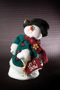 Christmas snowman plush toy a isolated on a dark patterned background with copy space Stock Images