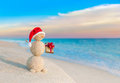 Christmas Snowman in Santa hat with gift at sunset beach Royalty Free Stock Photo