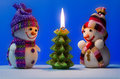 Christmas snowmen standing near the candle in the form of a tree Royalty Free Stock Image