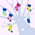 Christmas socks on winter tree, snowing behind Stock Photo
