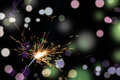 Christmas sparkler lighted on colorful lights background Royalty Free Stock Photos