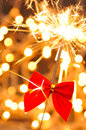 Christmas sparkler with red ribbon on blurred light background Royalty Free Stock Photos