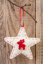 Christmas star decoration hanging against wooden background Royalty Free Stock Photos