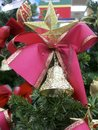 Christmas star and red bow a with a bell under it a on the top of an xmas tree Royalty Free Stock Photos