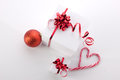 Christmas still with candycane gift boxes red ball and heart on light background Royalty Free Stock Image
