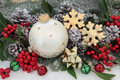 Christmas still life background with bauble decorations holly and winter greenery over snow Royalty Free Stock Images