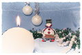 Christmas still life with burning candle and snowman toy Royalty Free Stock Photo