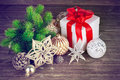 Christmas still life with fir gift and tinsel on wooden board Royalty Free Stock Photo