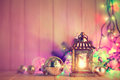 Christmas still life with lamp garland and balls on wooden board Royalty Free Stock Image