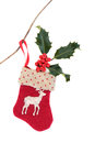Christmas stocking eve red with holly hanging on a twig over white background Stock Photos
