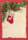 Christmas stocking eve reindeer with border of winter greenery and red bells over old parchment and red background Royalty Free Stock Photography