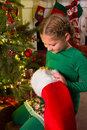 Christmas stocking and a girl young finding present in her Royalty Free Stock Photography