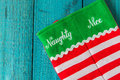 Christmas stocking holiday on vintage blue wooden background naughty or nice Stock Photography