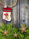 Christmas stocking a juvenile on a rope in front of a wooden wall with pine needles decorated with stores cover the bottom Royalty Free Stock Photos