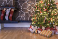 Christmas stockings and tree hanging on a fireplace next to a on morning Royalty Free Stock Images