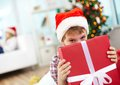 Christmas surprise portrait of cheerful boy peeking out of big red giftbox on evening Royalty Free Stock Image