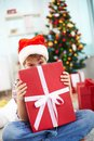 Christmas surprise portrait of cheerful boy peeking out of big red giftbox on evening Stock Photos