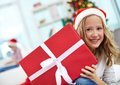 Christmas surprise portrait of happy girl peeking out of big red giftbox on evening Stock Photography