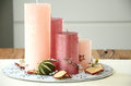 Christmas table decoration with four pink candles and dried fruits scattered Royalty Free Stock Photo