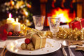 Christmas table with fireplace and christmas tree in the backgro a romantic dinner setting candles decorations a fire is burning Royalty Free Stock Photography
