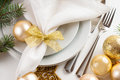 Christmas table setting in gold tones festive decorations with fir branches baubles decorations Stock Photo