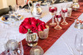Christmas table setting with red roses formal dinner and candles Stock Photo